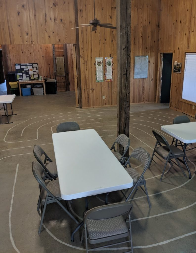 Image of main room with tables and chairs; open area left for group assembly.