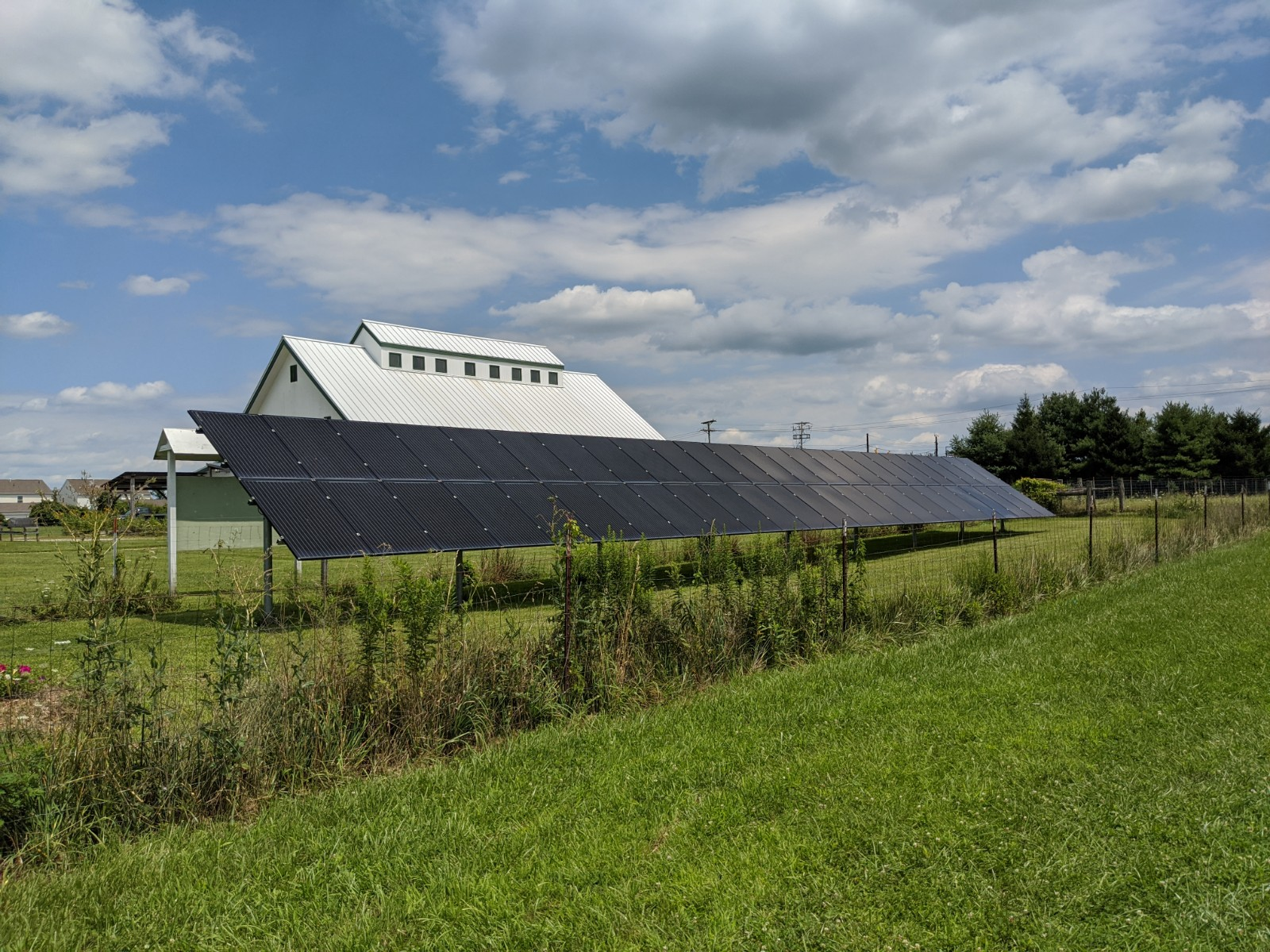 Fore ground: a row of solar panels. In the background roof outline of Shepherd's Corner's big white barn.