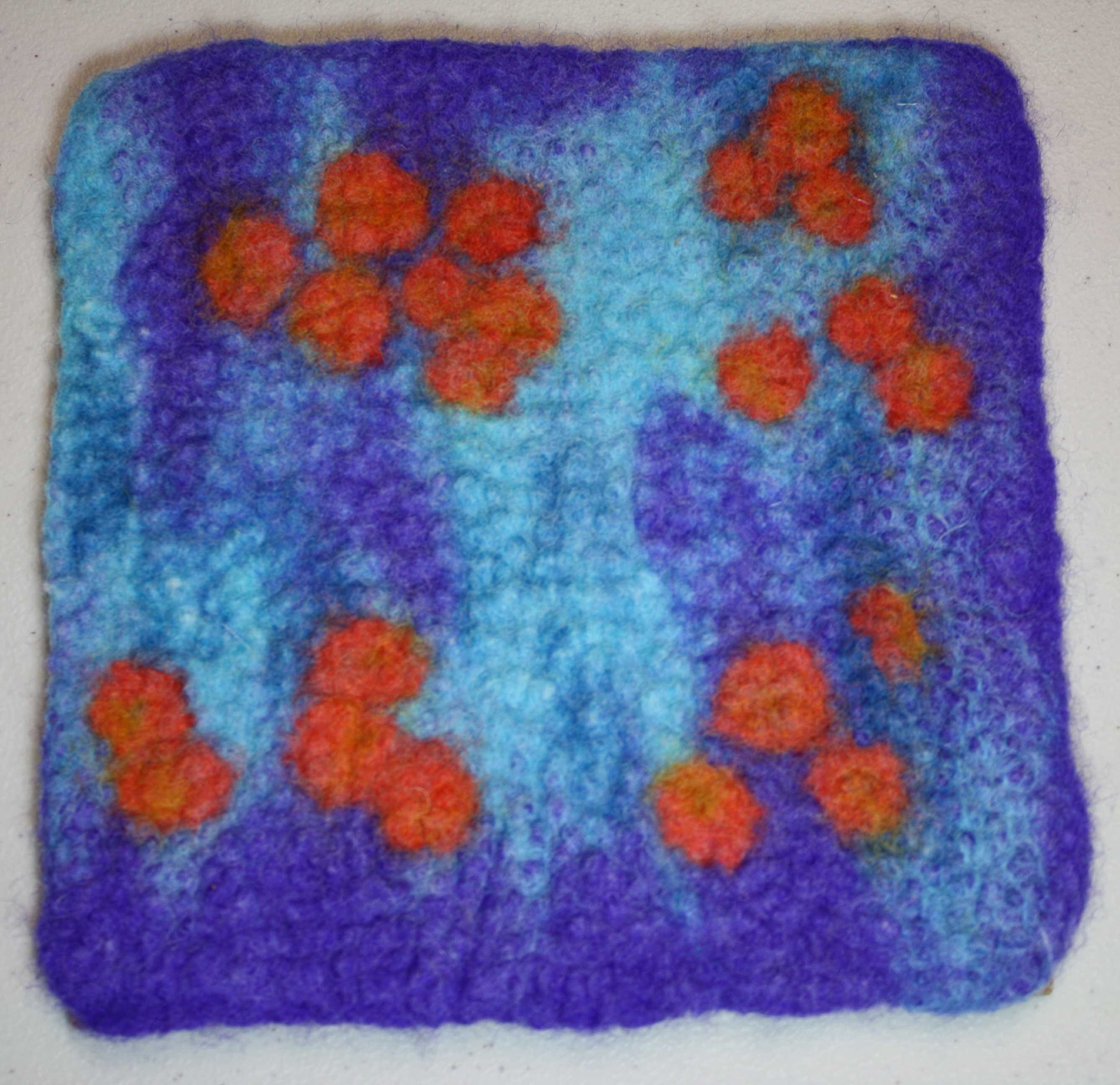 Felted square of deep and light blue wool decorated burnt orange circles of wool.