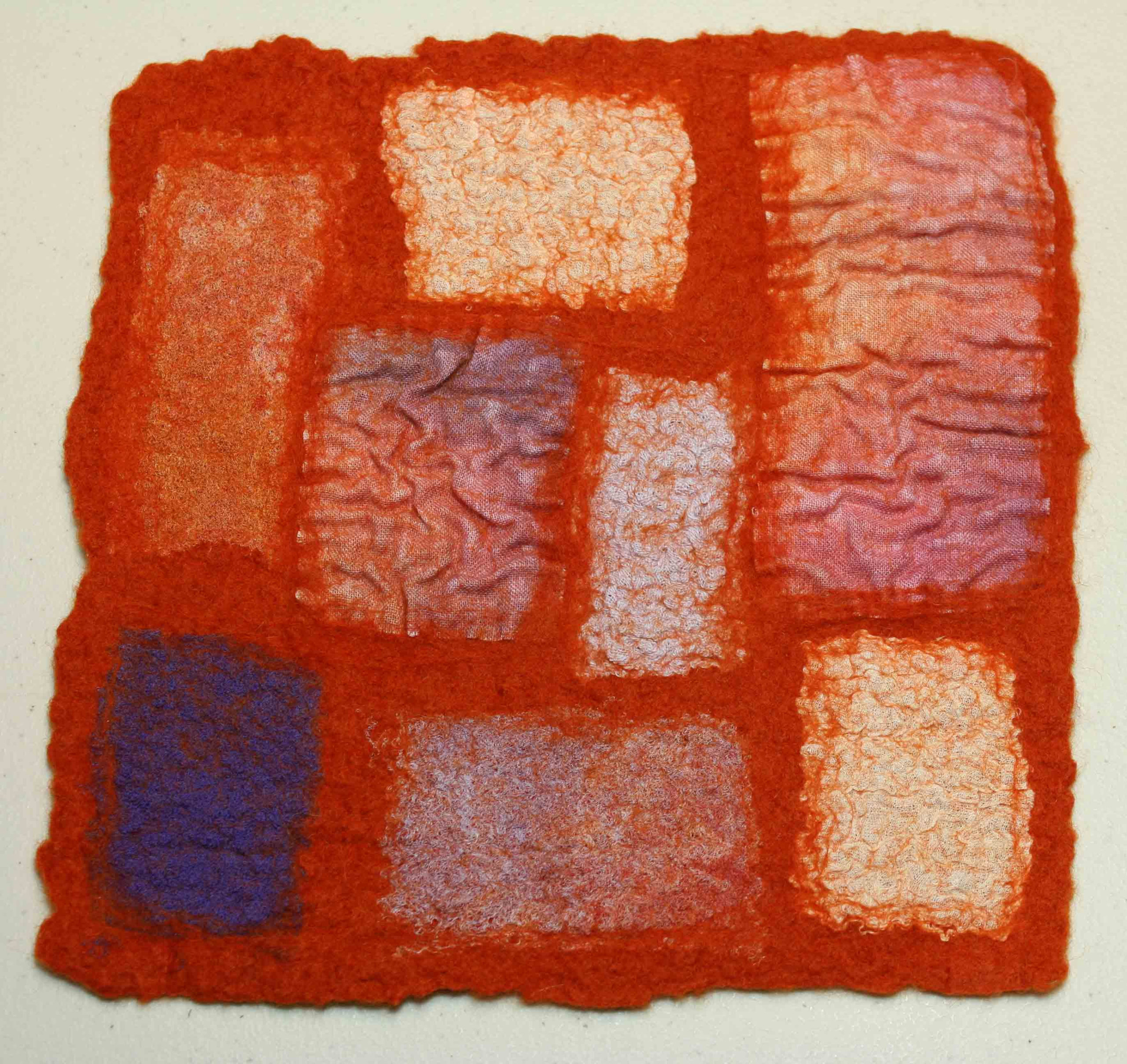 Red background felt square with squares of various sizes of light orange and blue wool.