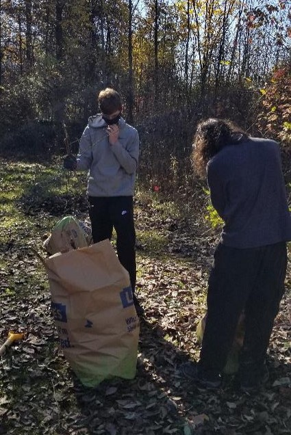 Two boy scouts working to bag invasive plants removed from the wetland area. They are working to fill a brown yard waste bag.