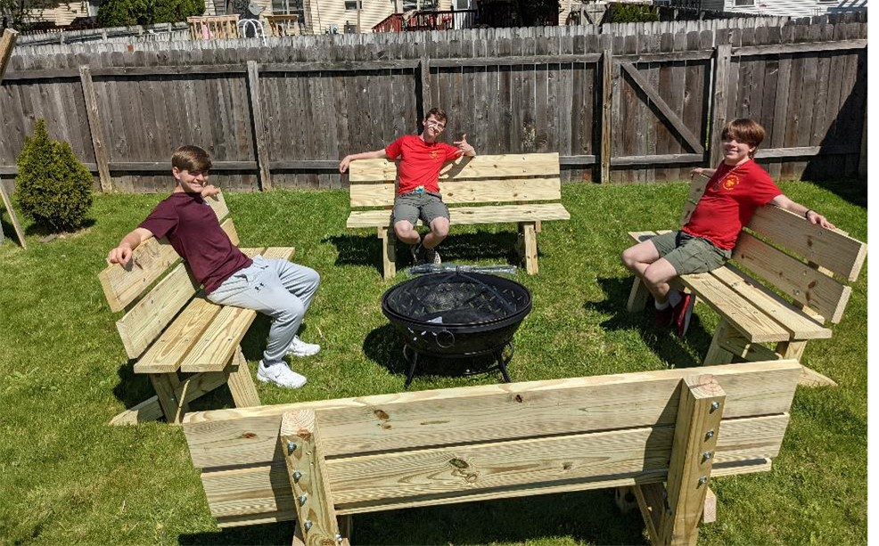Three boy scout troop members sitting on four new benches made for our meditation trail.