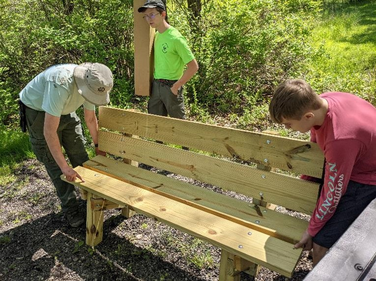 Three boy scout troop members placing the benches they have made on the meditation trail.