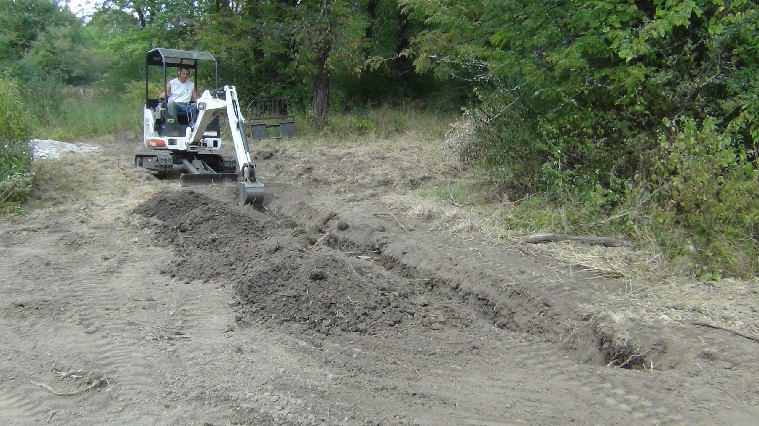 Individual on a bob cat, small digging device, digging a drainage trench in the exposed dirt.